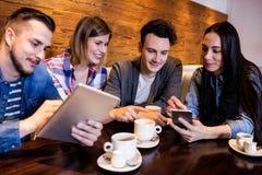 Amis avec le comprimé numérique et le téléphone portable au restaurant Photos stock