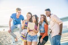 Amis avec le comprimé sur la plage Images libres de droits