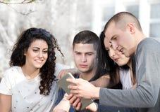 Amis avec le comprimé sur le banc Images libres de droits