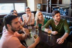Amis avec le football de observation de bière à la barre ou au bar Photographie stock libre de droits