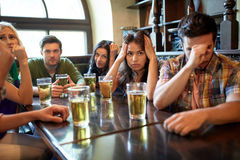 Amis avec le football de observation de bière à la barre ou au bar Image libre de droits