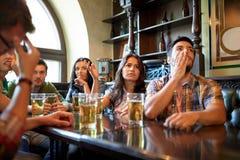 Amis avec le football de observation de bière à la barre ou au bar Images stock
