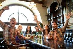 Amis avec le football de observation de bière à la barre ou au bar Photo libre de droits