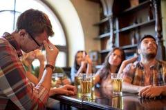 Amis avec le football de observation de bière à la barre ou au bar Images libres de droits