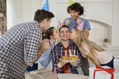 Amis avec le gâteau célébrant l'anniversaire à une partie Image libre de droits
