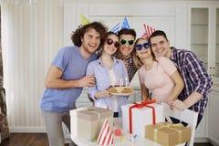 Amis avec le gâteau célébrant l'anniversaire à une partie Images libres de droits