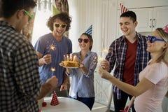 Amis avec le gâteau célébrant l'anniversaire à une partie Photographie stock libre de droits