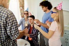 Amis avec le gâteau célébrant l'anniversaire à une partie dans la chambre Images stock