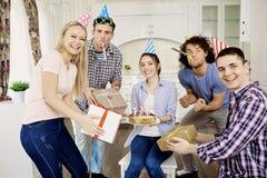 Amis avec le gâteau célébrant l'anniversaire à une partie dans la chambre Photo stock