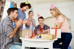 Amis avec le gâteau célébrant l'anniversaire à une partie dans la chambre Image stock