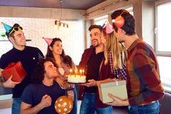 Amis avec le gâteau avec des bougies célébrant l'anniversaire à une partie Photographie stock