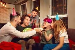 Amis avec le gâteau avec des bougies célébrant l'anniversaire Photographie stock