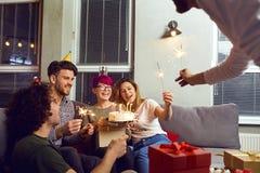 Amis avec le gâteau avec des bougies célébrant l'anniversaire Photos libres de droits
