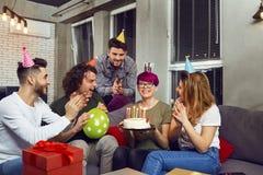 Amis avec le gâteau avec des bougies célébrant l'anniversaire Image libre de droits