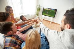 Amis avec le jeu de observation du football ou de football de bière Photo libre de droits