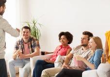 Amis avec le maïs éclaté et boissons parlant à la maison Image libre de droits