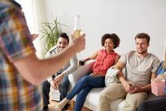 Amis avec le maïs éclaté et boissons parlant à la maison Images stock