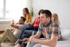 Amis avec le maïs éclaté et la bière regardant la TV à la maison Photo stock