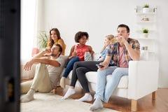 Amis avec le maïs éclaté et la bière regardant la TV à la maison Image libre de droits