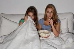Amis avec le maïs éclaté et la TV de observation à la maison Photos stock