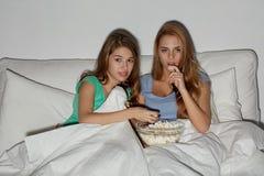 Amis avec le maïs éclaté et la TV de observation à la maison Photographie stock