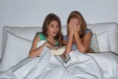 Amis avec le maïs éclaté et la TV de observation à la maison Photo stock