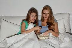 Amis avec le maïs éclaté et la TV de observation à la maison Photo libre de droits