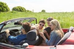 Amis avec le PC de comprimé conduisant dans la voiture de cabriolet Photos stock
