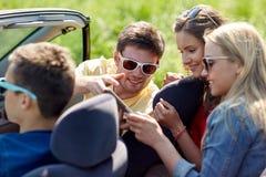 Amis avec le PC de comprimé conduisant dans la voiture de cabriolet Image libre de droits