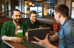 Amis avec le PC de comprimé et la bière verte au bar Photographie stock