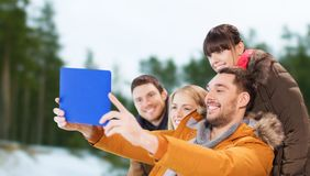 Amis avec le PC de comprimé prenant le selfie en hiver Photo stock