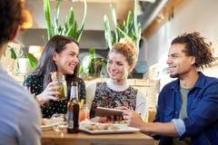 Amis avec le PC, les boissons et la nourriture de comprimé à la barre Image stock