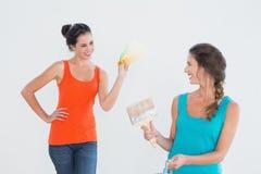 Amis avec le pinceau choisissant la couleur pour peindre une salle Images stock
