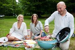 Amis avec le pique-nique de BBQ en parc Images stock