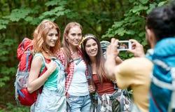 Amis avec le sac à dos photographiant par le smartphone Image libre de droits