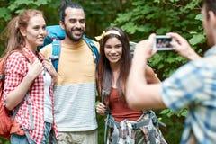 Amis avec le sac à dos photographiant par le smartphone Photographie stock