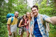 Amis avec le sac à dos prenant le selfie en bois Photos stock