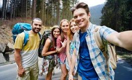Amis avec le sac à dos prenant le selfie en bois Photographie stock