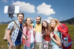 Amis avec le sac à dos prenant le selfie par le smartphone Photographie stock libre de droits