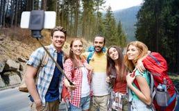 Amis avec le sac à dos prenant le selfie par le smartphone Image stock