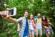 Amis avec le sac à dos prenant le selfie par le smartphone Photo stock