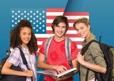 Amis avec le sac à dos se tenant contre le drapeau américain à l'arrière-plan Photo libre de droits