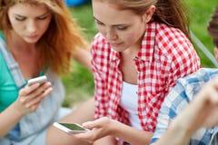 Amis avec le smartphone au camping Image stock