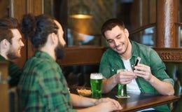 Amis avec le smartphone buvant de la bière verte au bar Photos libres de droits
