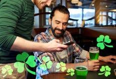 Amis avec le smartphone buvant de la bière verte au bar Photographie stock libre de droits