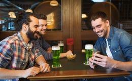 Amis avec le smartphone buvant de la bière verte au bar Image libre de droits