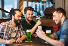 Amis avec le smartphone buvant de la bière verte au bar Image stock