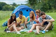 Amis avec le smartphone et la tente au camping Photos stock