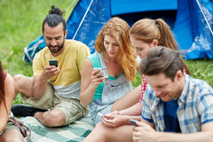 Amis avec le smartphone et la tente au camping Photographie stock libre de droits