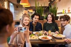 Amis avec le smartphone fotographing au restaurant Photo stock